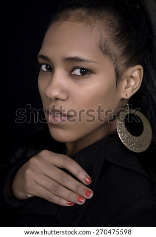 young beautiful african woman close up portrait, on black background - stock photo