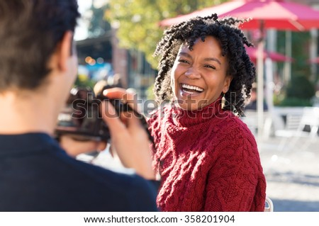 Young beautiful african woman posing for a photo. Boyfriend clicking a picture with camera of an smiling girlfriend. Happy woman having photos clicked by a photographer outside. Man taking a picture. - stock photo