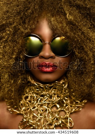 Young beautiful African woman posing in fashionable sunglasses and gold necklace. Studio shot - stock photo