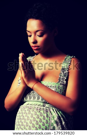 Young beautiful afro american pregnant woman praying against black background - stock photo