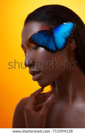 Young beautiful afro girl, vivid image with blue butterfly