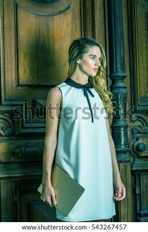 Young beautiful American Business Woman working in New York, wearing sleeveless white dress with black collar, holding laptop computer, standing by vintage style office door way. Color filtered effect