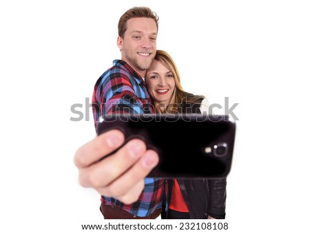 young beautiful American couple in love taking romantic self portrait selfie photo together with mobile phone smiling happy wearing trendy clothes isolated on white background  - stock photo