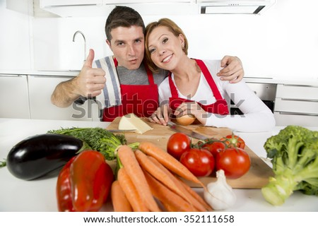 young beautiful American couple working at home kitchen  in red apron preparing vegetable salad together smiling happy in husband and wife cooking team and healthy fresh food concept  - stock photo