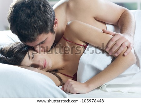 Young beautiful amorous couple making love in bed - stock photo