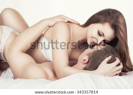 Young beautiful amorous couple making love in bed on white background - stock photo