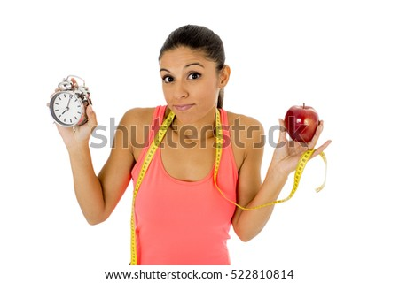 young beautiful and fit hispanic woman holding alarm clock apple fruit and taylor measure tape in healthy nutrinion and time for sport and diet concept isolated on white background
