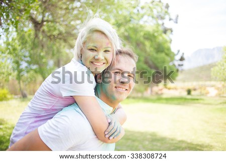 Young, Beautiful and funky couple playing with powder water paint on the Holi Festival