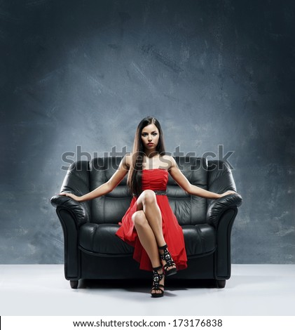 Young, beautiful and glamour woman in red dress sitting on the black leather sofa