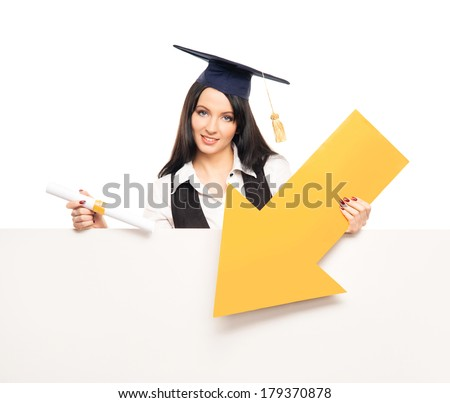 Young, beautiful and happy graduate girl pointing on a blank banner and smiling isolated on white