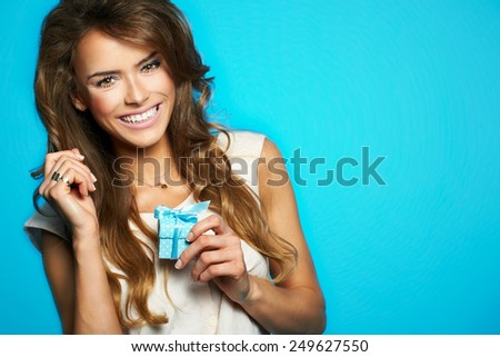 Young beautiful and happy woman with a gift - stock photo