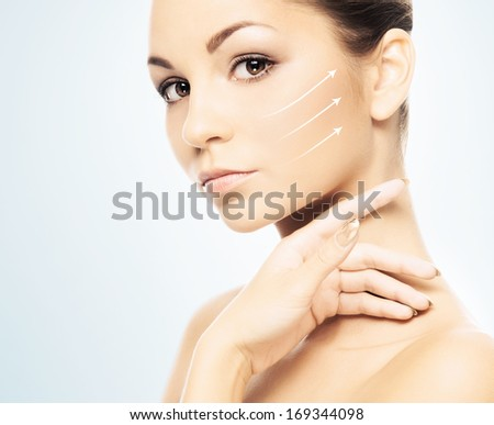 Young, beautiful and healthy girl with the arrows on her face (spa, surgery, face lifting and make-up concept collage) - stock photo