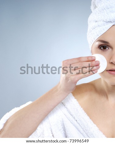 Young, beautiful and healthy young woman in bath clothes over grey background - stock photo