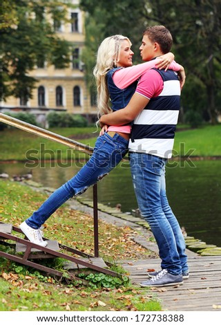 Young beautiful and passionate couple is expressing their feelings towards each other while hanging at a park