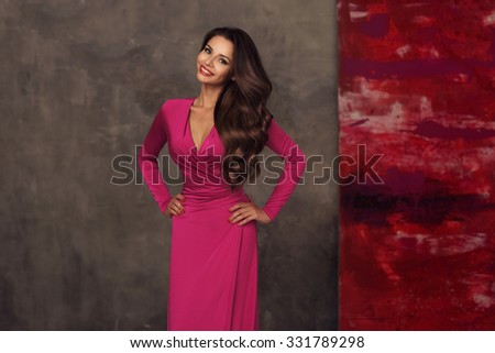 Young beautiful and pretty elegant woman in long pink evening dress posing against gray wall. Portrait of smiling happy cheerful girl - stock photo