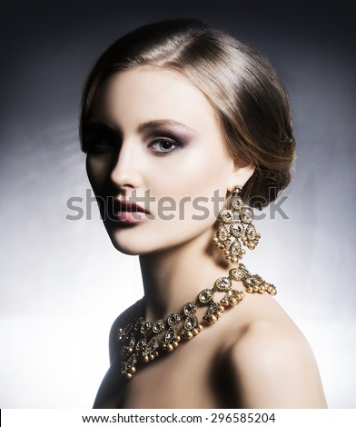 Young, beautiful and rich woman in jewels. Metal background  - stock photo