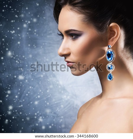 Young, beautiful and rich woman in jewels of platinum and stones over winter Christmas background - stock photo