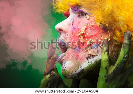 Young beautiful and sensual woman wearing a curly yellow wig with bright headpiece and androgynous chinese asian dragon styled face art and green hands  - stock photo