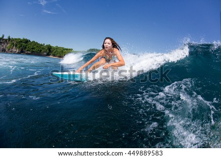 Young beautiful and sexy girl in a bikini surfing on a wave
