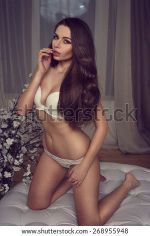 Young beautiful and sexy girl in white underwear posing on sofa - stock photo