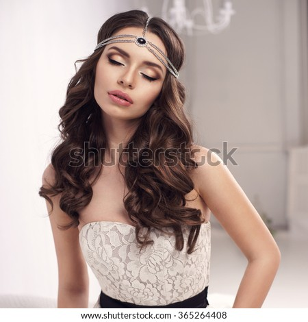Young beautiful and sexy woman posing in white dress in white interior. Fashion vogue style portrait of stylish sexy sensual girl with long curly brunette hair - stock photo