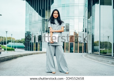 Young beautiful asian business woman standing with laptop in hand on background of business center - stock photo