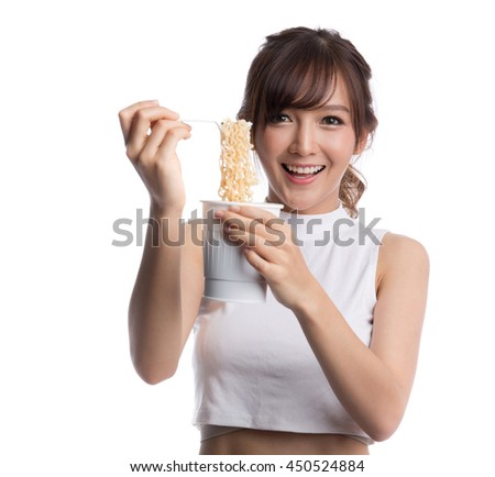 Young beautiful asian girl eating instant noodle using plastic fork. - stock photo