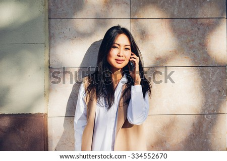 young beautiful Asian girl speaks by smart-phone, illuminated by the rays of sunset - stock photo