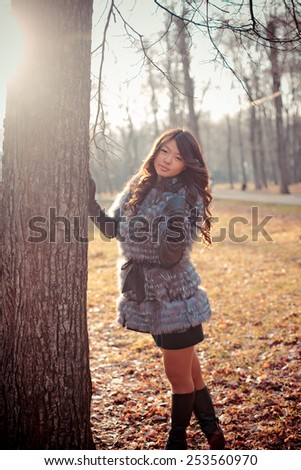 young beautiful asian girl with long hair in a fashionable fur coat walks in autumn park