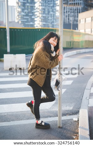 young beautiful asian hipster long brown straight hair woman leaning on a pole, laughing - carefreeness, happiness, youth concept
