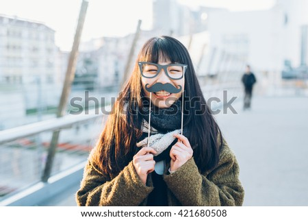Young beautiful asian hipster woman in the city with funny fake eyeglasses and mustache, looking in camera smiling - happiness, carnival, having fun concept