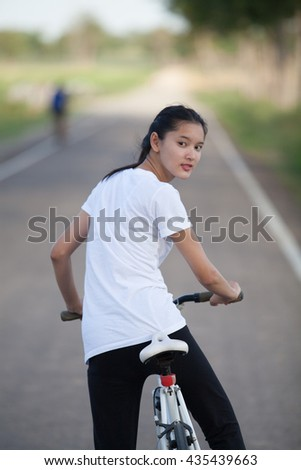 young beautiful asian woman and bicycle outdoors