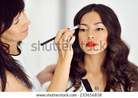 Young beautiful asian woman applying make-up by make-up artist - stock photo