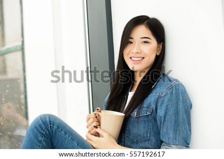 young beautiful asian woman drinking coffee or tea and looking outside on big modern windows
