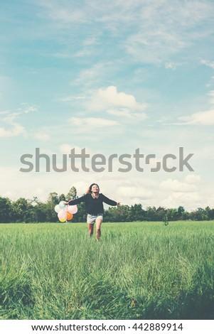 young beautiful asian woman holding balloon on green grassland running enjoy fresh air - stock photo