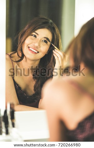 Young Beautiful Asian Woman making make-up near mirror - vintage effect filter
