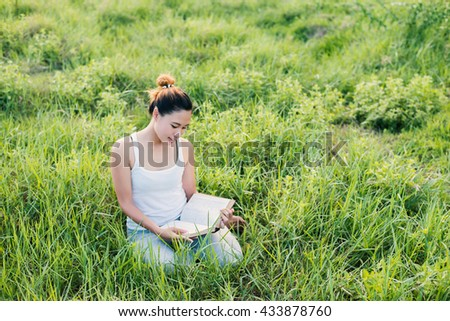 Young beautiful asian woman sitting and reading book in the meadows.