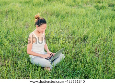 Young beautiful Asian woman using Laptop on nature meadows.
