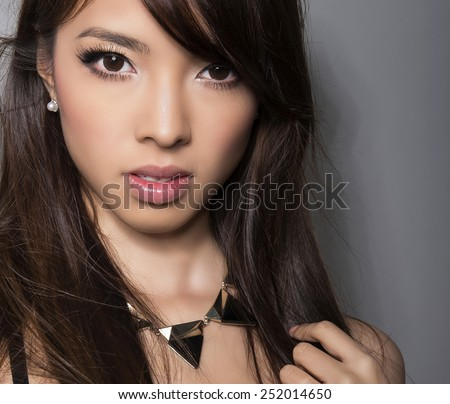 young beautiful asian woman with perfect skin and pretty make-up and brown hair. Sexy Lipstick, highlighter and rouge on clear skin - stock photo