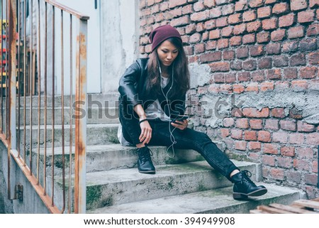 Young beautiful asiatic woman sitting on a staircase listening music with earphones and smart phone hand hold - music, technology, social network concept - stock photo