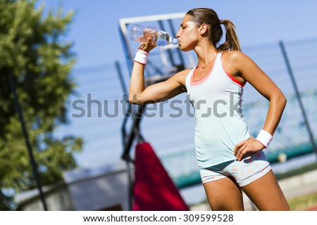 Young beautiful athlete drinking water after exercising to revitalize - stock photo