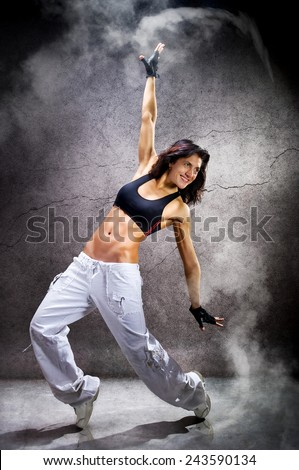 Young beautiful athletic woman dancing modern dance hip-hop on wall background with smoke - stock photo