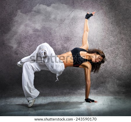 Young beautiful athletic woman dancing modern style dance hip-hop on studio on wall background with smoke