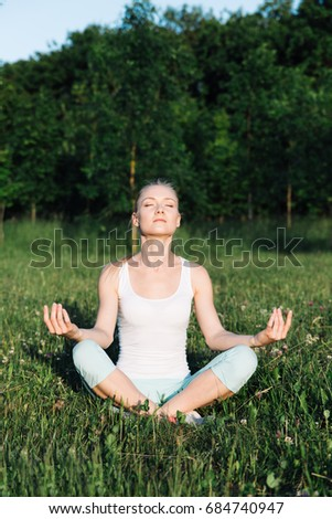 Young beautiful athletic woman doing yoga in the park