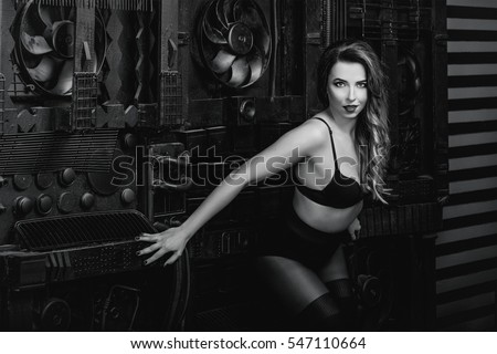 Young beautiful attractive and hot long hair woman in black underwear on industrial background in photo studio monochrome