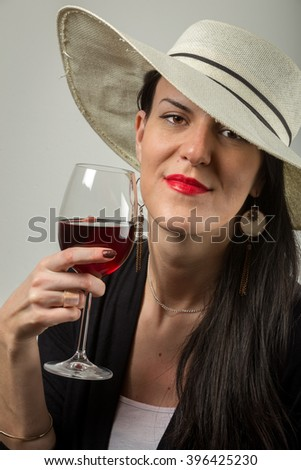 Young, beautiful, attractive lady with top hat in Valentines day tasting red dry wine with affection. - stock photo