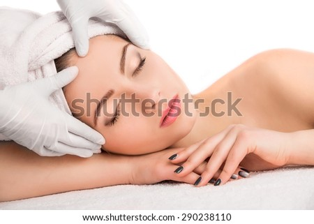 Young beautiful  attractive woman receiving facial massage and spa treatment over white background. Perfect Skin. Skincare. Young Skin - stock photo