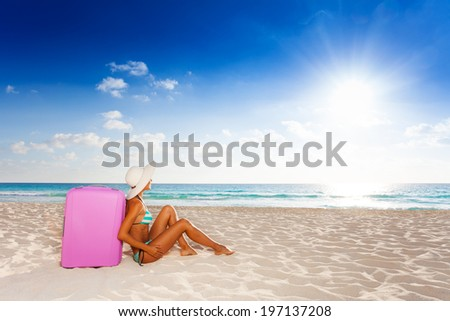 Young beautiful attractive woman sitting on the beach with pink suitcase wearing white straw hat