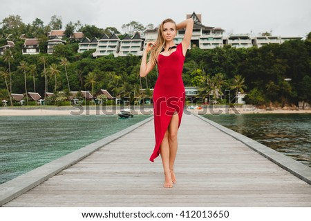 young beautiful attractive woman standing alone on pier in luxury resort hotel, summer vacation, red long dress, blond hair, sexy apparel, tropical beach, seductive, sensual, smiling - stock photo