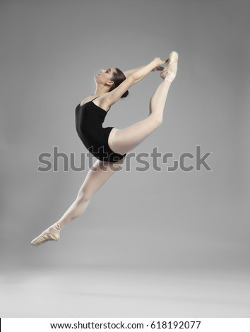 Young beautiful ballerina dancing on light background